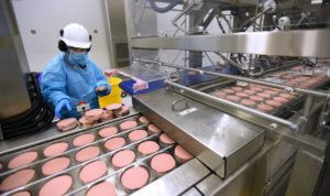 Frontline food worker wearing an N95 mask and inspecting processed meat