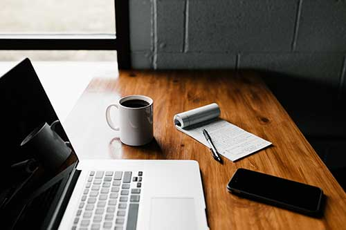 An image of the laptop and a mug of coffee